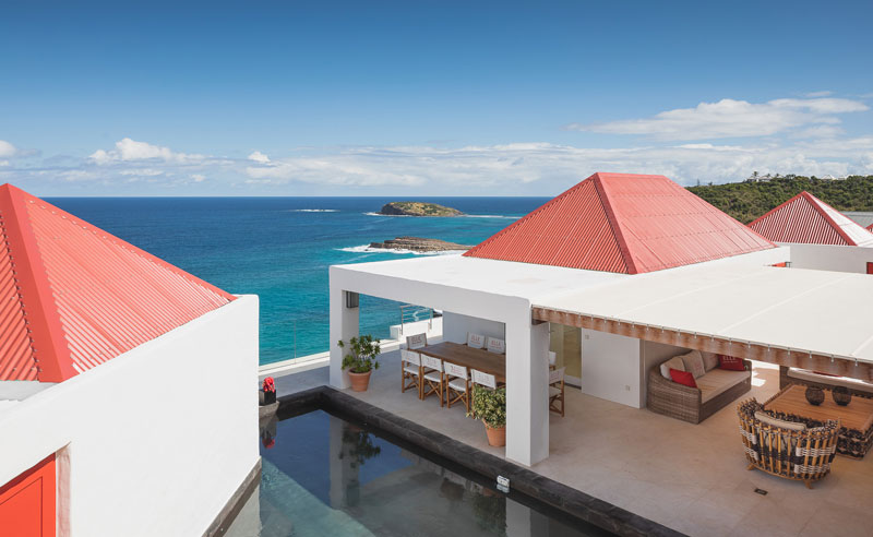 View of the blue ocean, swimming pool, outdoor dining table and roof of Elle Villa from the top