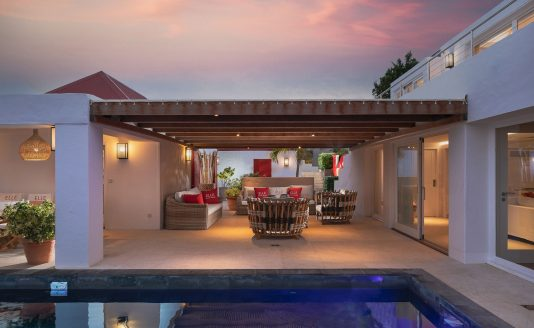 Outdoor view of swimming pool and patio under a purplish-pink sky